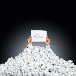 bigstock-Person-under-crumpled-pile-of--31906979