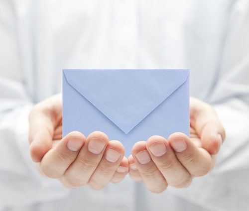 Blue paper envelope in hands
